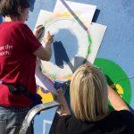 Spraying the Art Week Exeter background. Photo credit: Mark Cotton.